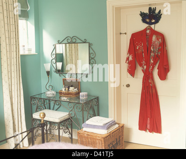Ornate metalwork dressing table with matching stool and mirror in turquoise bedroom with red silk kimono on door - Stock Photo