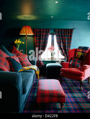 Red tartan upholstered stool and matching cushions on turquoise velvet sofa and red armchair in turquoise green - Stock Photo