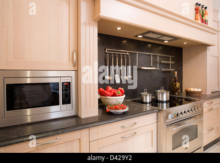 Utensils on rack above built in hob in nineties kitchen for Kitchen utensils in spanish