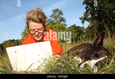 Berlin, Germany, a woman with her laptop on the lawn next to her dog - Stock Photo