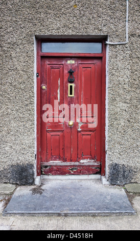 A distressed red door with peeling paint in an old house - Skerries, co.Dublin, Ireland - Stock Photo