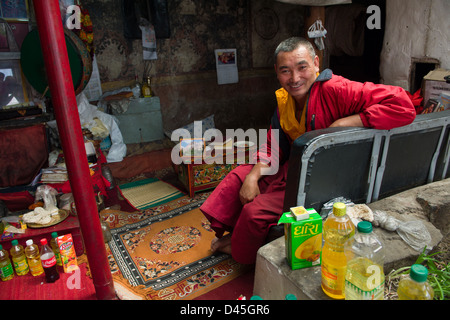 Monk sitting in an ante-room at Spituk Gompa, Leh, (Ladakh) Jammu & Kashmir, India - Stock Photo