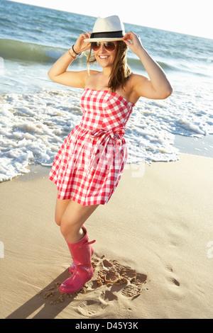 Teenage Girl Wearing Wellington Boots Splashing In Sea On Beach Holiday - Stockfoto