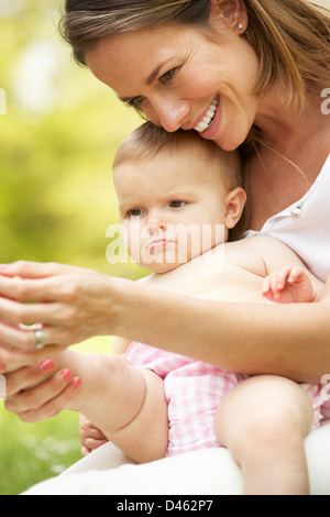 Mother Sitting With Baby Girl In Field Of Summer Flowers - Stock Photo
