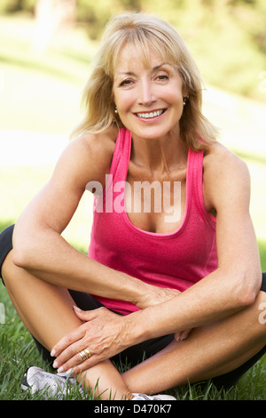 Senior Woman Resting After Exercising In Park - Stock Photo