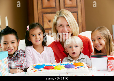 Mother Celebrating Child's Birthday With Friends - Stock Photo