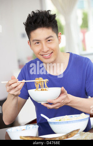 Young Chinese Man Sitting At Home Eating Meal - Stockfoto