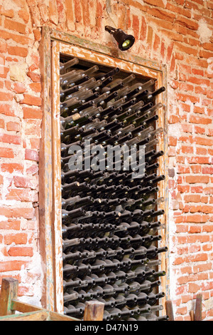 old wine bottles left in a niche on the wall - Stock Photo