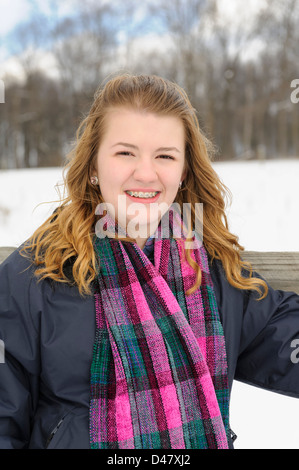 Teenage girl outdoors in winter snow portrait, wearing braces, blond hair, and pretty scarf. - Stockfoto