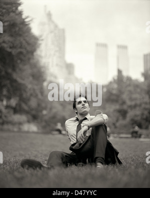 Young Professional Man Sitting in Central Park on a Lunch Break - Stock Photo