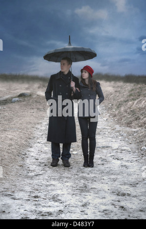a couple is doing a walk in the rain - Stock Photo