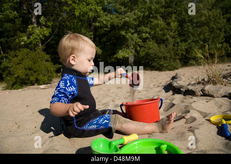 Child playing with sand at the beach - Stock Photo