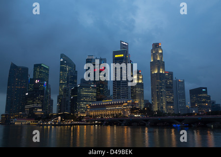 Marina bay in Singapore, 20th of February 2012, The fullerton hotel and skyscrapers of business area in dusk - Stock Photo