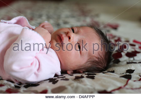A close up of a tiny newborn baby girl with long hair. - Stockfoto