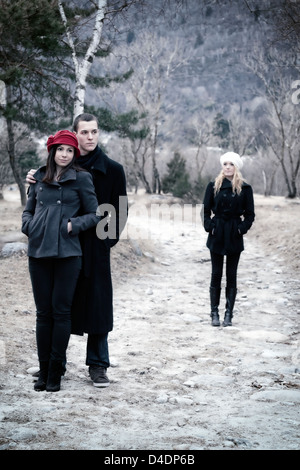 a couple arm in arm and a second woman is left behind - Stock Photo