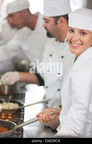 Chefs cooking in restaurant kitchen - Stock Photo