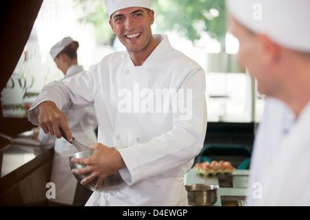 Chefs cooking in restaurant kitchen - Stock Photo