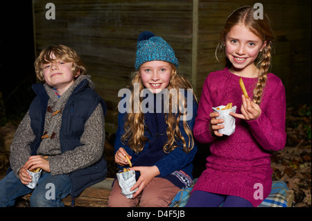 Smiling children eating french fries at night - Stock Photo