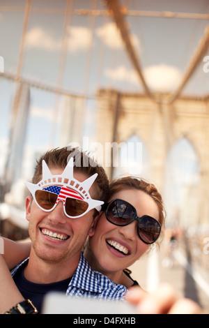 Couple in novelty sunglasses taking picture on urban bridge - Stockfoto
