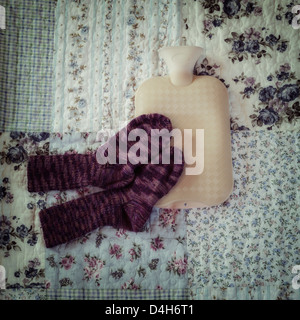 hot-water bottle with hand knitted socks on a vintage bed - Stockfoto