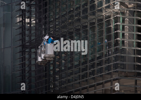 Two window cleaners work from the safety of a hanging cradle as they clean the glass of an office complex in the - Stock Photo
