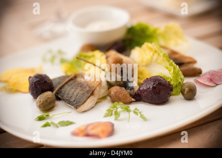 Plate of fish with salad and olives - Stock Photo