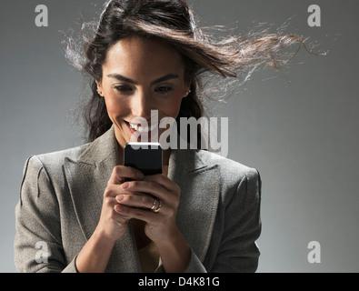 Businesswoman using cell phone - Stockfoto