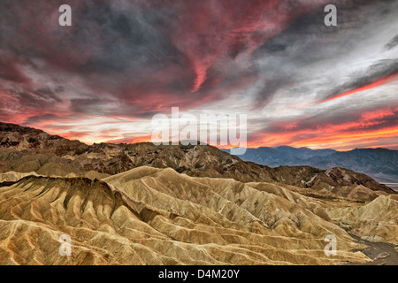 Spectacular sunset develops over Golden Canyon from Zabriskie Point and California's Death Valley National Park. - Stock Photo