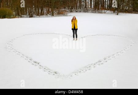 Woman making heart shape in snow - Stock Photo