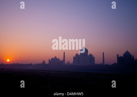 Sunrise over the Taj Mahal viewed from mehtab bagh park, across the dried up river Yamuna - Stock Photo