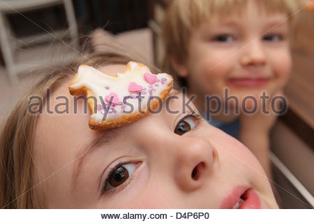 Handewitt, Germany, a child balancing a Plaetzchen on the face - Stock Photo
