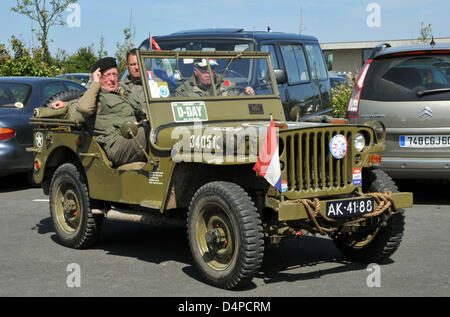 An US Jeep from World War II with Dutch passengers drives around on a parking lot in Point-du-Huc, France, 04 June - Stock Photo