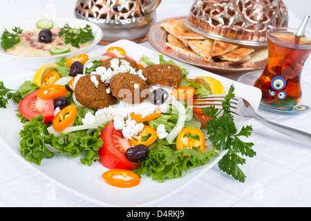 Falafel Salad with Pita Bread and Hummus plate, complimented with tea on a white table cloth. - Stockfoto