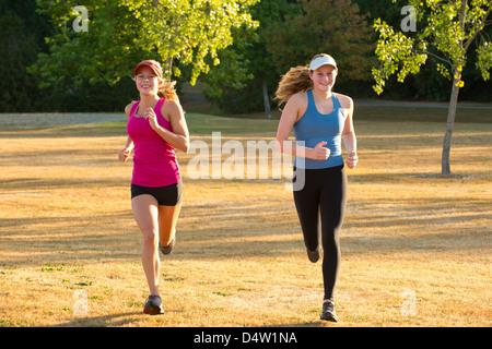 Teenage girls running together in field - Stockfoto