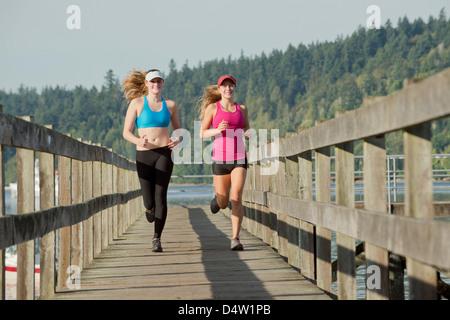 Teenage girls running on wooden dock - Stockfoto