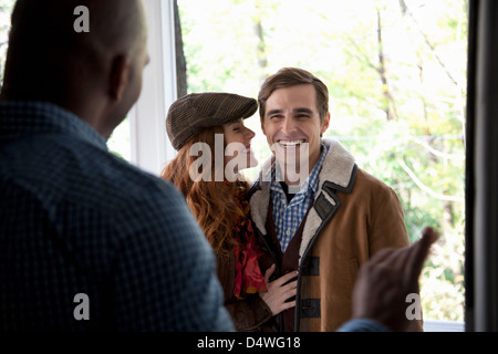 Smiling couple at front door - Stock Photo