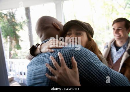 Friends hugging at front door - Stock Photo