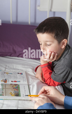 Mother helps child to read - Stock Photo