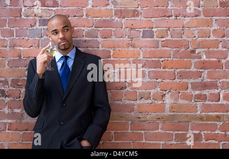 Young business man leaning against the brick wall, thinking and drinking wine. - Stock Photo