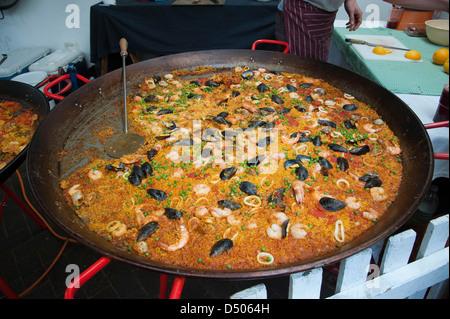 Large pan of Paella cooking - Stock Photo