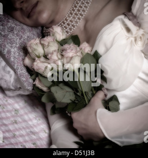 a woman in bed with a bouquet of pink roses - Stock Photo