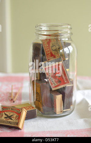 A jar of vintage matchboxes - Stock Photo