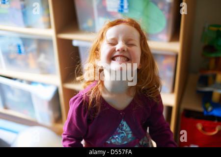 Girl making face in playroom - Stockfoto