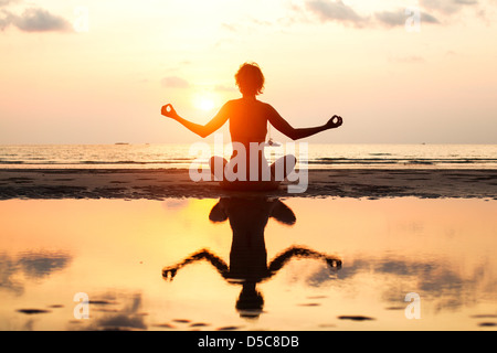 Yoga woman sitting in lotus pose on the beach during sunset, with reflection in water, in bright colors. - Stock Photo