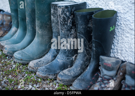 A row of green and black muddy wellington boots all lined up against a wall after a family walk in the English countryside - Stock Photo