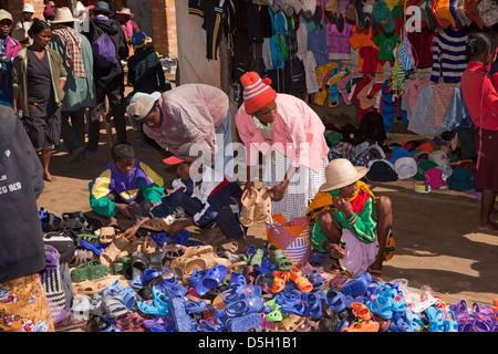 Madagascar, Ambositra, Marche Sandrandahy market, customers at shoe stall - Stock Photo