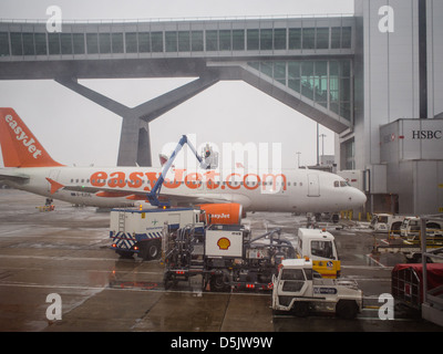 An easyJet aircraft is refuelled and de-iced during poor weather conditions at London Gatwick airport. - Stock Photo