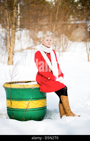 Young woman sitting on empty big painted flowerpot - Stockfoto