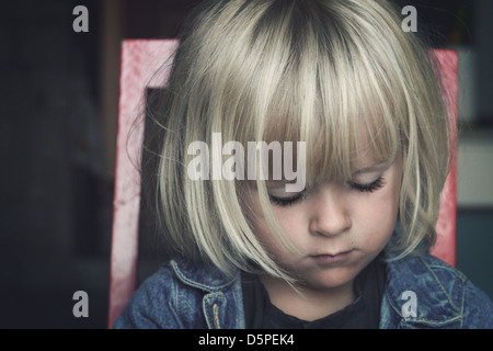 Sad little child sitting on a chair, looking down - Stock Photo