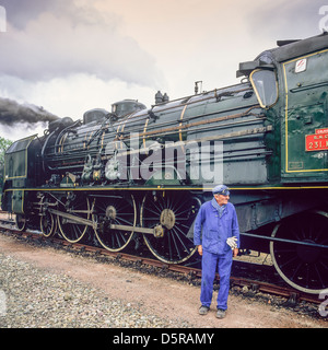 Engineer with historic steam locomotive 'Pacific PLM 231 K 8' of 'Paimpol-Pontrieux' train Brittany France - Stock Photo